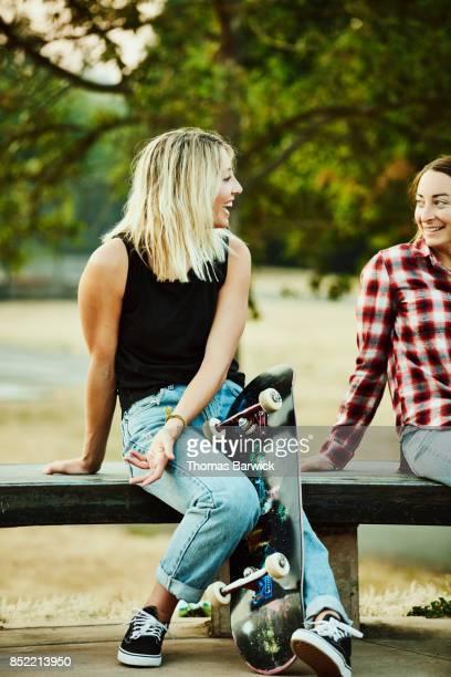 Smiling friends in discussion after skateboarding together in skate park