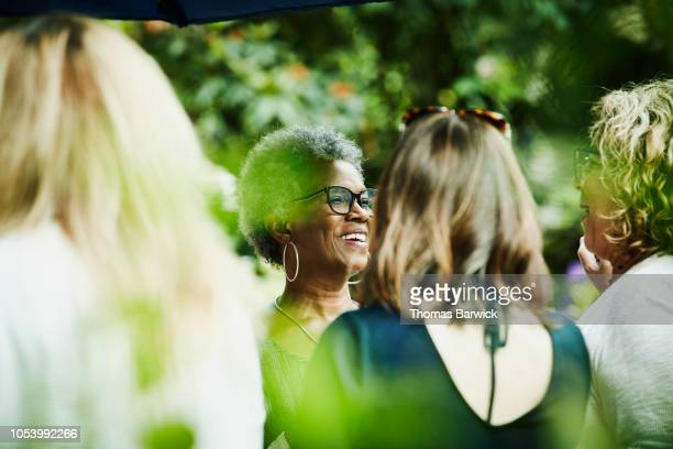 smiling friends in discussion during backyard garden party - 50 59 years stock pictures, royalty-free photos & images