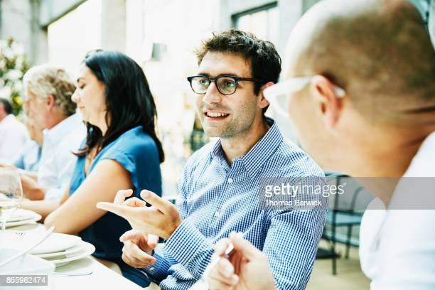 Smiling friends in discussion during celebration dinner on outdoor patio