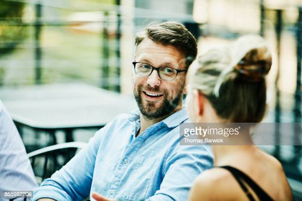 smiling friends in discussion during dinner party on summer evening - 35 39 jahre stock-fotos und bilder