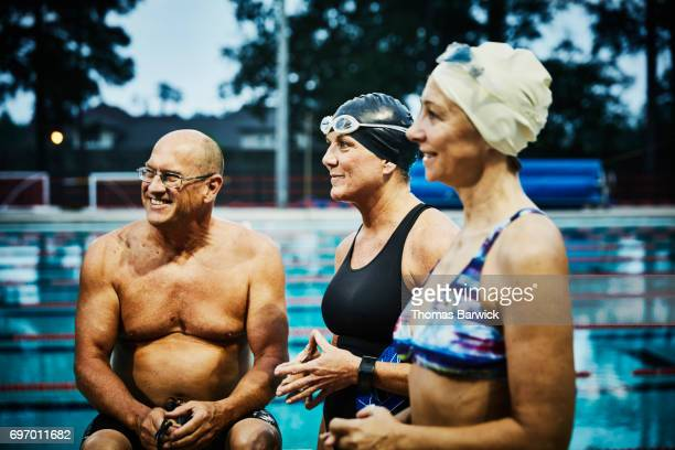 Smiling friends in discussion on outdoor pool deck before early morning workout