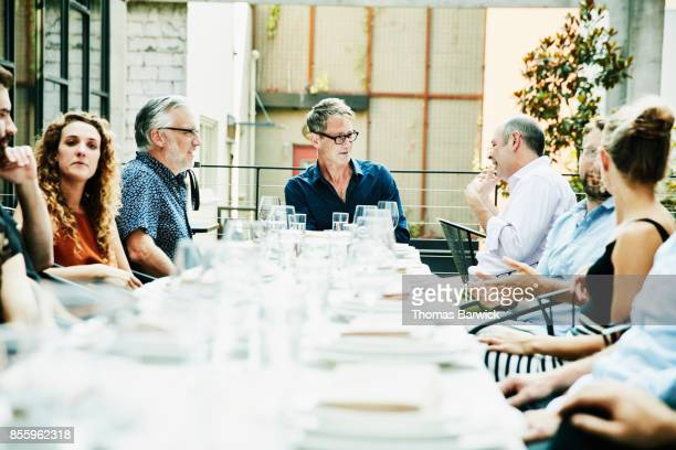 smiling friends in discussion while sharing a meal on outdoor patio - ereignis atmosphäre stock-fotos und bilder