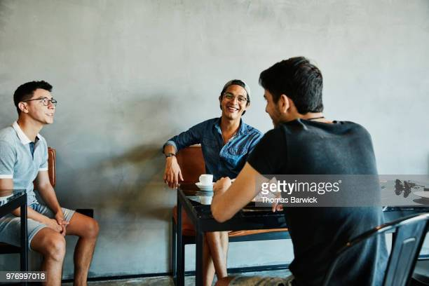smiling friends in discussion while sharing coffee in bakery - carefree stock pictures, royalty-free photos & images
