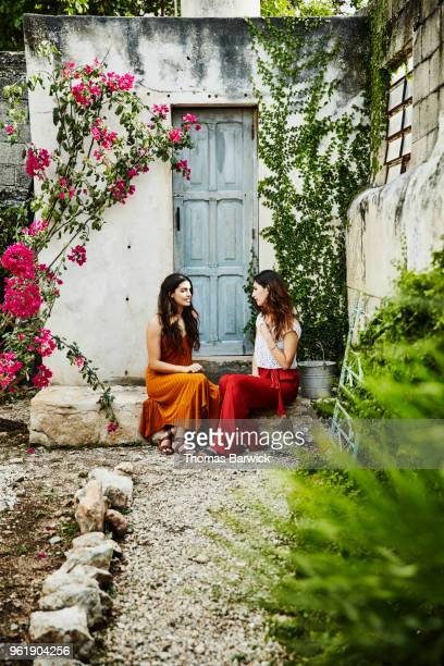 Smiling friends in discussion while sitting in courtyard at outdoor spa
