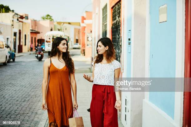smiling friends in discussion while walking through town during vacation - red pants stock pictures, royalty-free photos & images