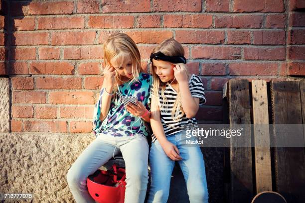 Smiling friends listening music while sitting against brick wall