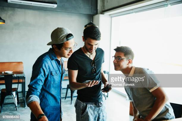 Smiling friends looking at smartphone while waiting for order in coffee shop