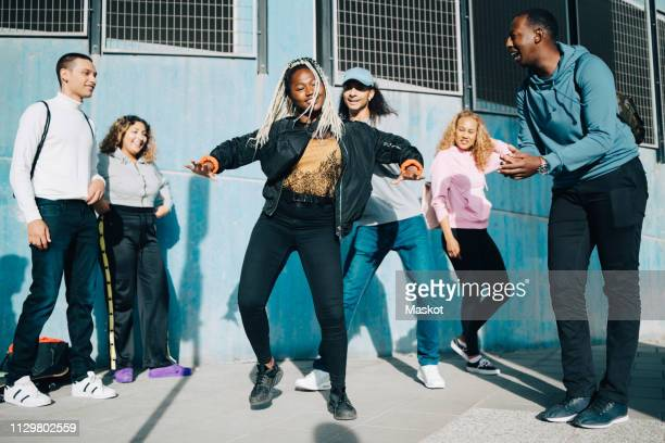 smiling friends looking at teenage girl dancing on sidewalk in city - a la mode photos et images de collection