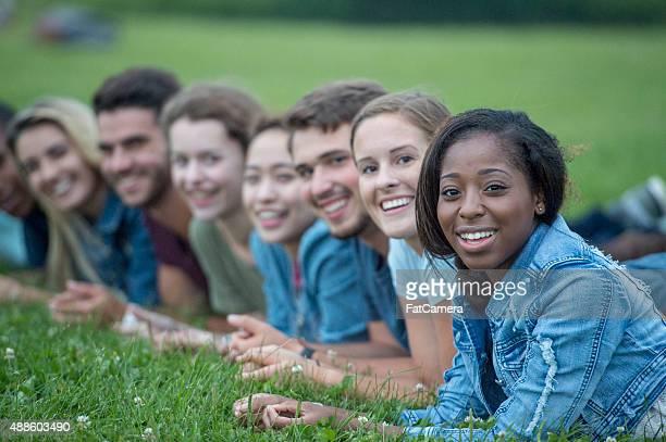 Lächelnd Freunde liegen in einer Reihe