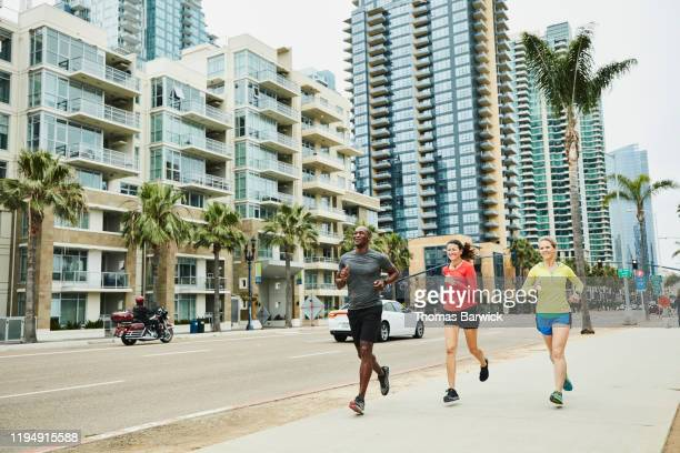 smiling friends on morning run in city - center athlete stock pictures, royalty-free photos & images