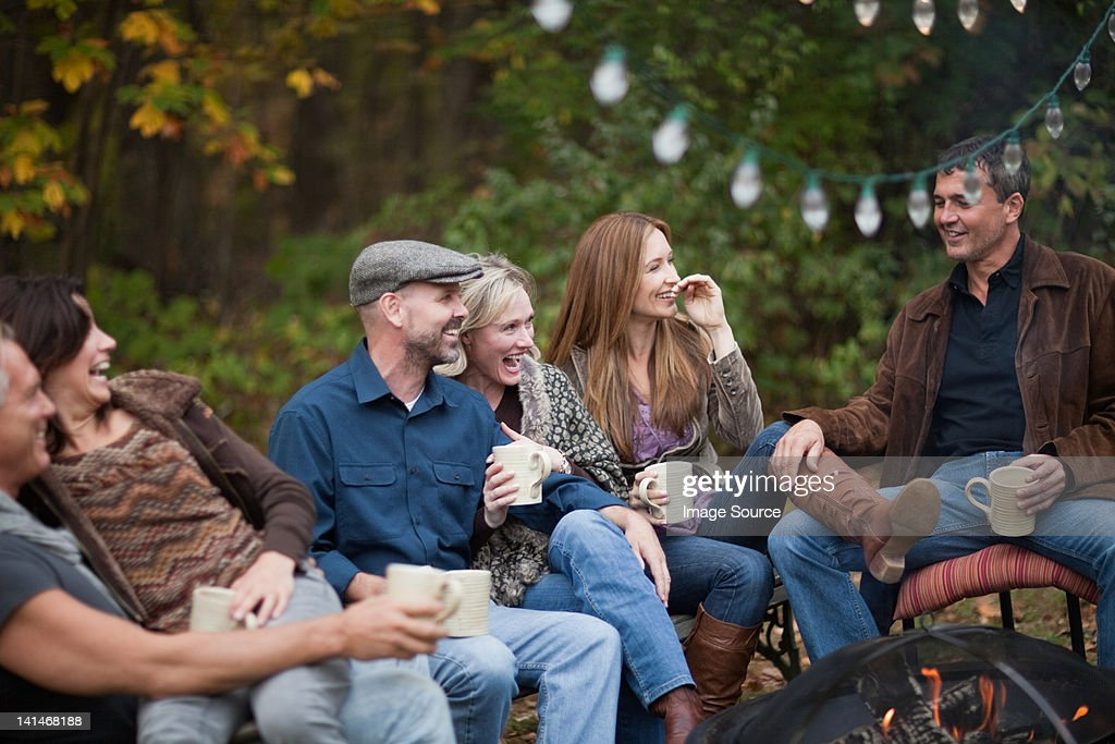 Smiling friends outdoors by fire : Stock-Foto