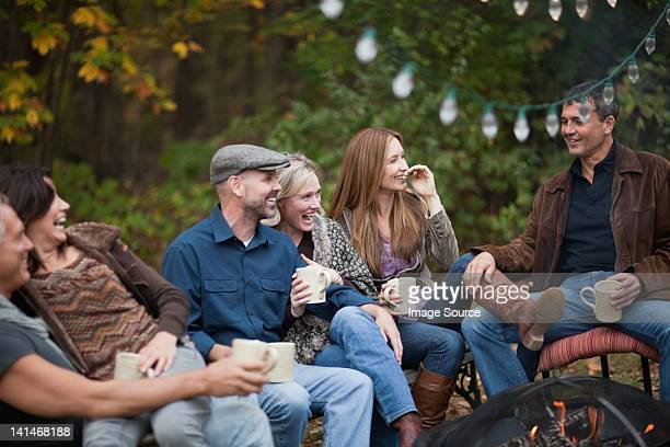 smiling friends outdoors by fire - 35 39 jahre stock-fotos und bilder