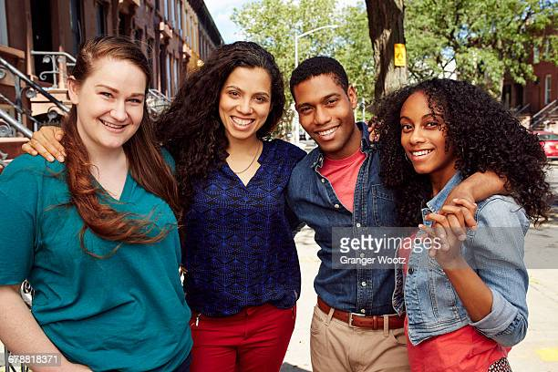 Smiling friends posing on city sidewalk