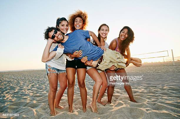 Smiling friends posing together on beach