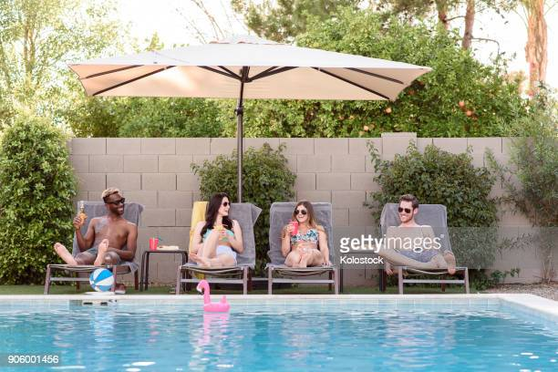 Smiling friends relaxing and drinking poolside