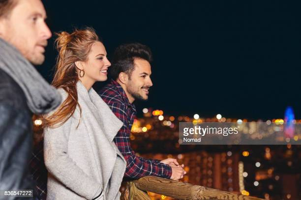 Smiling friends relaxing by illuminated city
