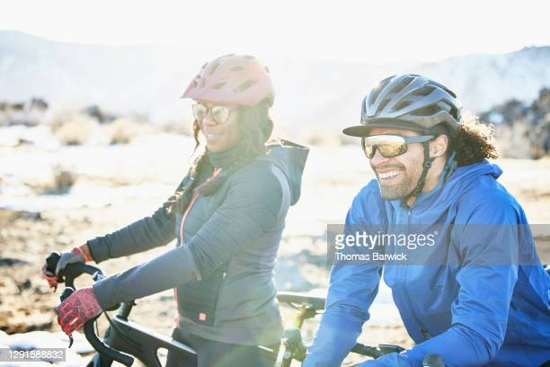 smiling friends relaxing during gravel bike ride on winter afternoon - sunglasses stock pictures, royalty-free photos & images