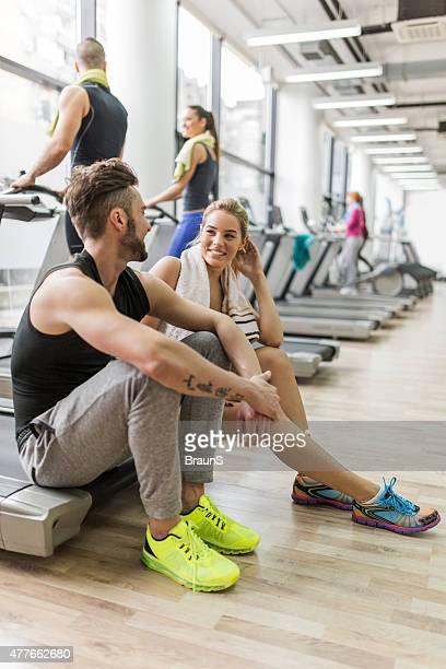 Souriant amis de détente en faisant de l'exercice dans la salle de sport et de la communication