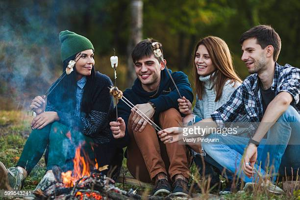 Smiling friends roasting marshmallows in forest