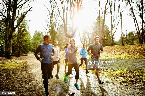 smiling friends running together in park - sportkleding stock pictures, royalty-free photos & images