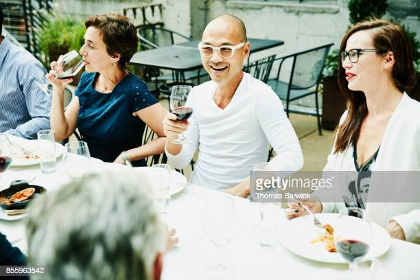Smiling friends sharing dinner on restaurant patio on summer evening