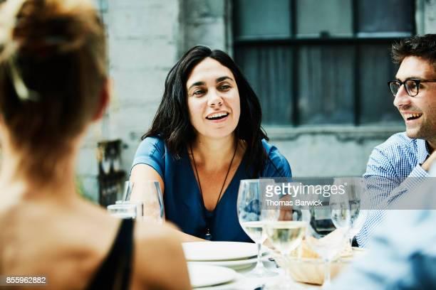 Smiling friends sharing dinner on restaurant patio
