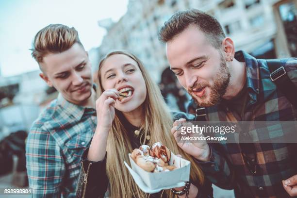 smiling friends sharing donuts and having a great time - fete stock photos and pictures