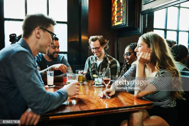 Smiling friends sharing drinks at table in bar