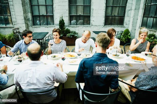 Smiling friends sharing family style meal on restaurant patio