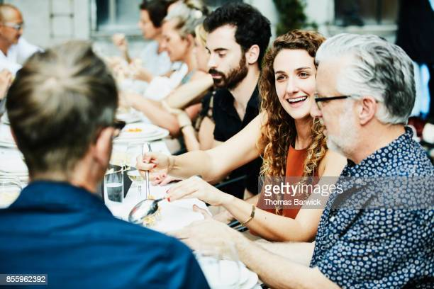 Smiling friends sharing food during celebration dinner on restaurant patio