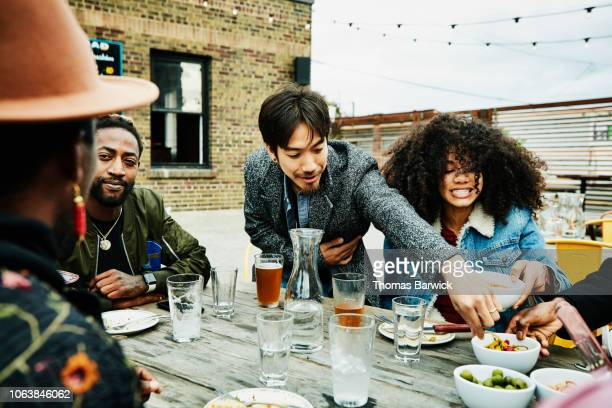 smiling friends sharing food during party at outdoor bar - outdoor party imagens e fotografias de stock