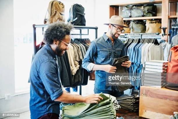 Smiling friends shopping in mens clothing boutique