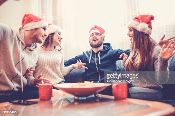 smiling friends singing to celebrate christmas eve together at home - eggnog stock photos and pictures
