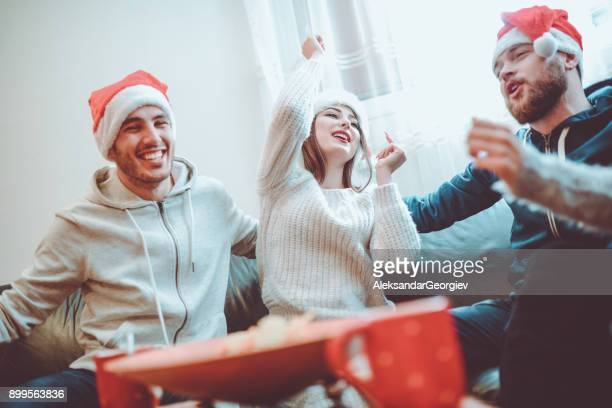 Smiling Friends Singing to Celebrate Christmas Eve Together at Home
