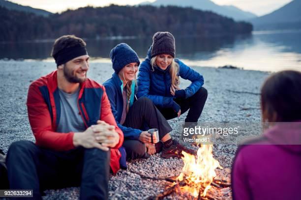 smiling friends sitting around campfire at lakeshore - camping stock-fotos und bilder