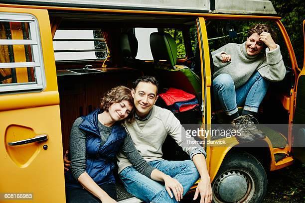 smiling friends sitting in van after hike - landvoertuig stockfoto's en -beelden