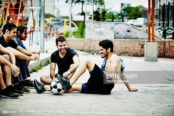 Smiling friends sitting together on court in park