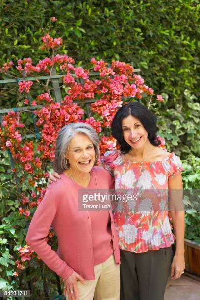 smiling friends standing in garden - only mature women stock pictures, royalty-free photos & images