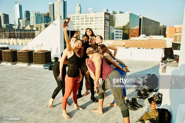 smiling friends taking group selfie after rooftop yoga class - friendly match stockfoto's en -beelden