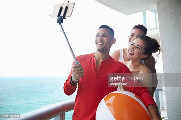 Smiling friends taking selfie on balcony