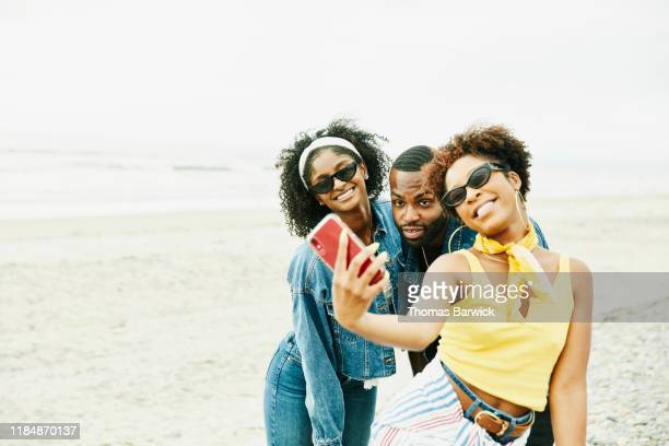 smiling friends taking selfie with smart phone on beach - travel stock pictures, royalty-free photos & images