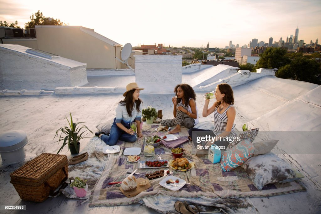 Smiling friends talking while having food at party on building terrace : Stock Photo