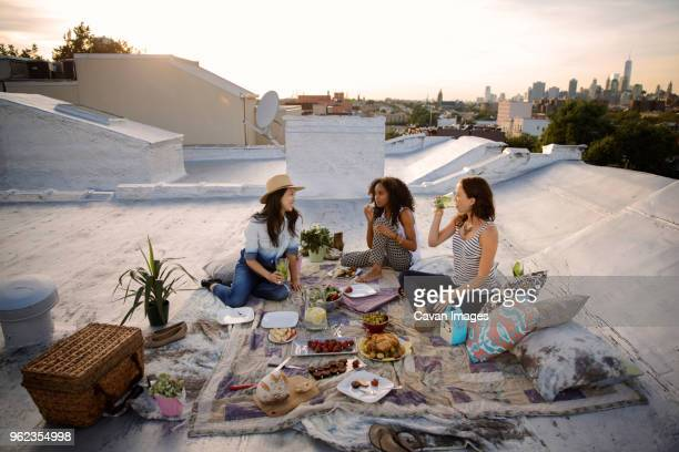 smiling friends talking while having food at party on building terrace - cavan images foto e immagini stock