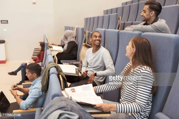 smiling friends talking while studying at auditorium in university - theaterzaal stockfoto's en -beelden