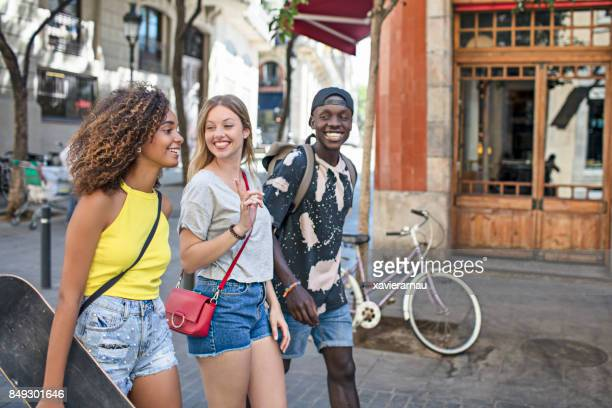smiling friends talking while walking in city - generation z stock pictures, royalty-free photos & images