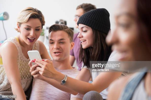 Smiling friends texting on cell phone
