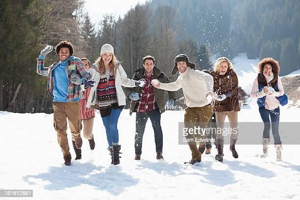 Sonriendo amigos tirando snowballs en el campo