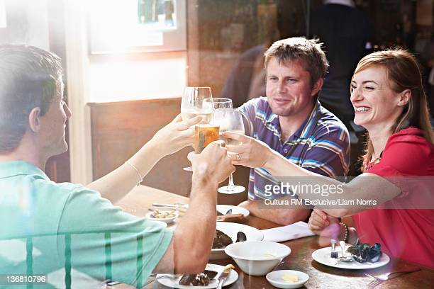 Smiling friends toasting in restaurant