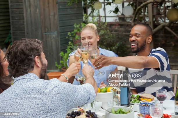 Smiling friends toasting with champagne glasses at garden patio table