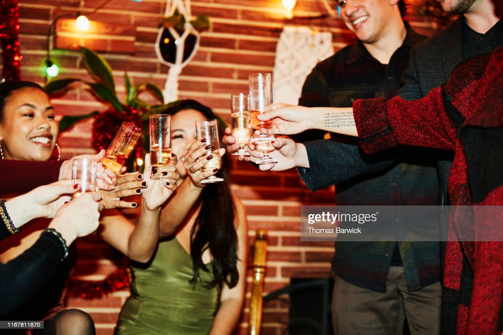 Smiling friends toasting with champagne glasses during holiday party in home : Stock Photo